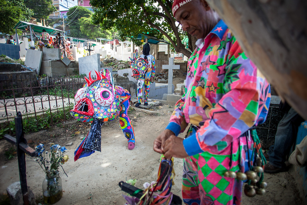 Un integrante de los Diablos baila rindiendo homenaje sobre la tumba de un familiar durante la festividad del Corpus Christi, representada en Venezuela a traves del ritual magico-religioso de los Diablos Danzantes. Los Diablos de Naiguata se identifican por pintar sus propios trajes y decorarlos con cruces, rayas y circulos, figuras que impiden que el maligno los domine. Las mascaras son en su gran mayoria animales marinos. Llevan escapularios cruzados, crucifijos y cruces de palma bendita. Naiguata, 30 Mayo 2013. (ivan gonzalez)