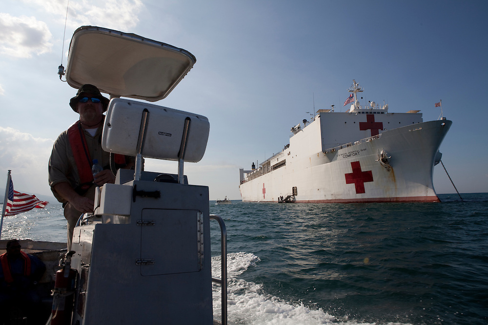 Third mate Joe Kranz drives a utility boat to scout locations to retrieve patients from the shore by boat and bring them to the USNS Comfort, a naval hospital ship, right, for treatment on Wednesday, January 20, 2010 in Port-Au-Prince, Haiti. The Comfort deployed from Baltimore, bringing nearly a thousand medical personnel to care for victims of Haiti's recent earthquake.