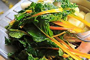 Swiss chard leaves and stalks on kitchen sink drainer with peeled potatoes