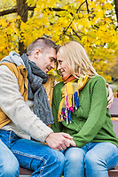 Portrait of handsome man sitting while showing affection to his beautiful wife in park