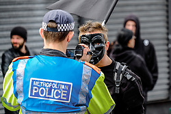 An anti-fascist protester confronts a police officer during a march held by the English Defence League. Walthamstow London May 2015