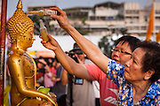 13 APRIL 2014 - BANGKOK, THAILAND:  Women bathe a Buddha statue in scented oils at Bangkok City Hall. Many people go to temples and religious ceremonies to make merit on Songkran. Songkran is celebrated in Thailand as the traditional New Year's Day from 13 to 16 April. Songkran is in the hottest time of the year in Thailand, at the end of the dry season and provides an excuse for people to cool off in friendly water fights that take place throughout the country. Songkran has been a national holiday since 1940, when Thailand moved the first day of the year to January 1.   PHOTO BY JACK KURTZ