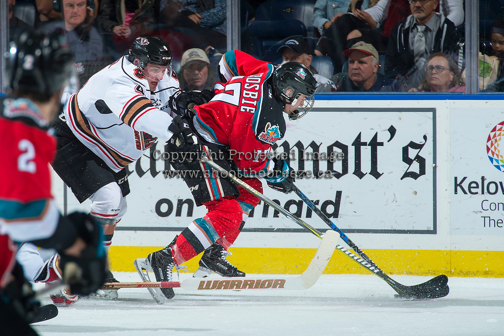 KELOWNA, CANADA - OCTOBER 13: Layne Toder #4 of the Calgary Hitmen stick checks from behind Kyle Crosbie #17 of the Kelowna Rockets during second period on October 13, 2017 at Prospera Place in Kelowna, British Columbia, Canada.  (Photo by Marissa Baecker/Shoot the Breeze)  *** Local Caption ***