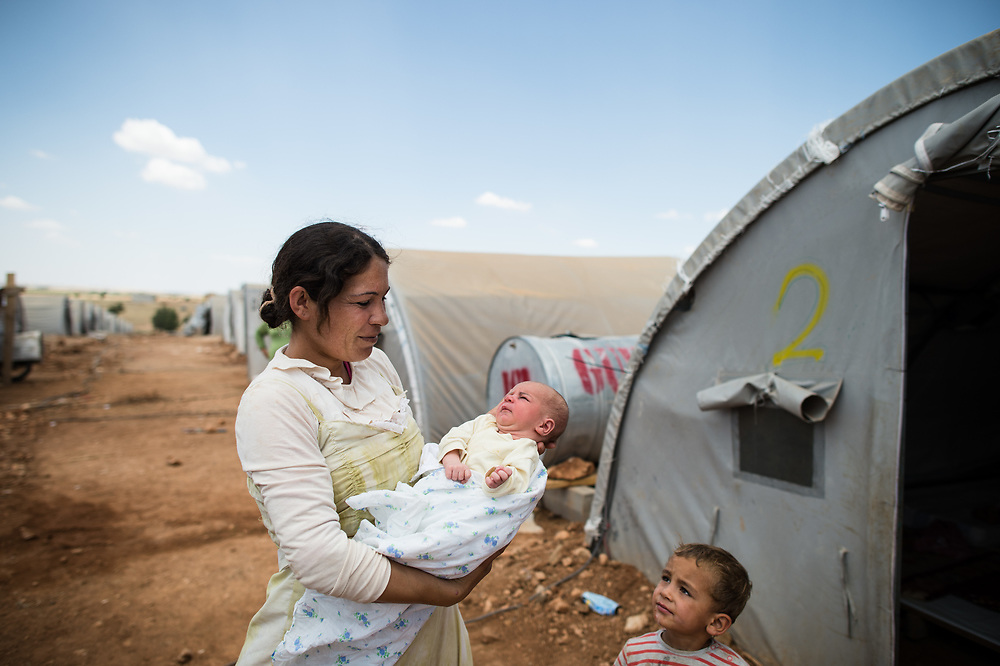 39-year-old Kurd Sami Habash with her six days old son and son Ahmad in the IDP camp of Kobane. Sami fled with her family from ISIS first to Turkey and than to Kobane. Approximately 35 families are accomodated there in 350 tents. Kobanê (Ayn al-Arab), Syria, June 20, 2015