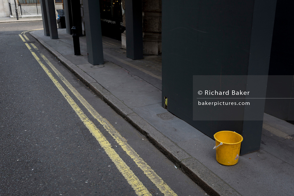 A single yellow bucket and double-yellow lines, in St james's, London, England.