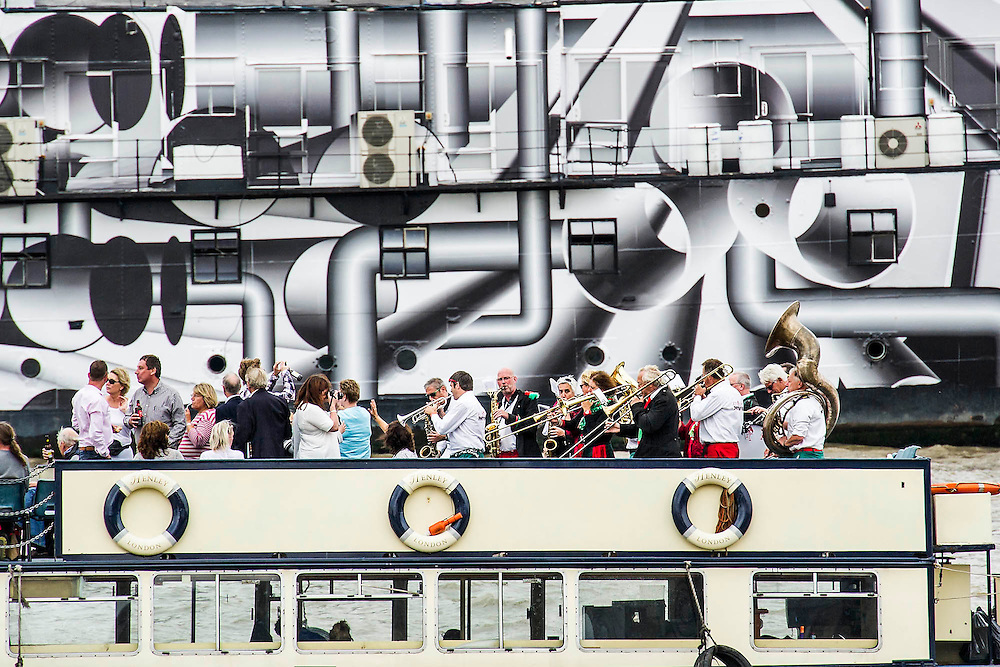 A brass band provides support as the boats pass HMS President which has been painted in 'Dazzle' camouflage paint in commemoration of WW1, The Great River Race, London's River Marathon (also known as The UK Traditional Boat Championship) - a 21.6 Miles boat race up the River Thames from London Docklands to Ham in Surrey. It attracts over 300 crews from all over the globe and appeals to every level of competitor from those who enjoy fun, fancy dress and charity stunts, to serious sportsmen. River Thames, London, 27 September 2014.