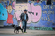 A man walking a dog reads the interesting graffiti on a wall near Nørrebro and Outer Frederiksberg