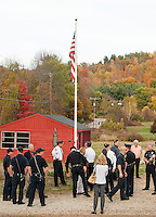 Gilford Town Officials, Police, Fire and Public Works personnel gather for the Flagpole dedication ceremony in honor of the first responders held at the Gilford Outing Club/Warming Hut on Tuesday afternoon.   (Karen Bobotas/for the Laconia Daily Sun)