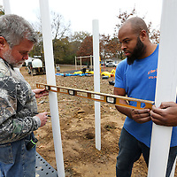 Adam Robison | BUY AT PHOTOS.DJOURNAL.COM<br /> Charlie Usery, owner of Newcreation LLC, in Farmington Missouri, measures out and levels new posts with worker Mike Mosby, as they work on installing new playground equipment at Chandler Park in Tupelo Monday afternoon.
