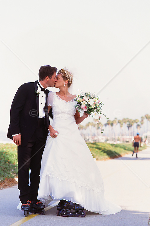 bride and groom on roller blades kissing