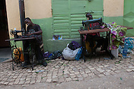 Two Harari men work at their craft on German sewing machines on the street in Harar, Ethiopia, named Makina Girgir. The street takes its name from the mulitiple sewing machines that adorn the cobblestones and the sounds they all make when working in tandem.