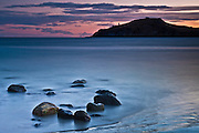 Sunrise at Shelly Beach, with Taiaroa Lighthouse and Otago Peninsula in the distance