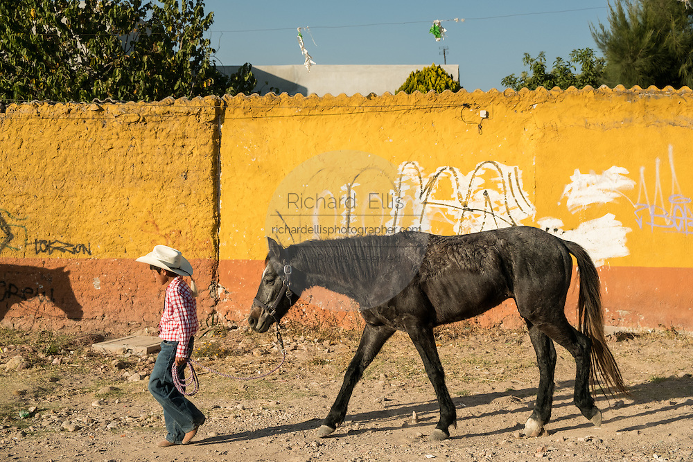 A young Mexican cowboys leads his horse after arriving to camp at a village stop along the road during the annual Cabalgata de Cristo Rey pilgrimage January 4, 2017 in La Sauceda, Guanajuato, Mexico. Thousands of Mexican cowboys and horse take part in the three-day ride to the mountaintop shrine of Cristo Rey stopping along the way at shrines and churches.