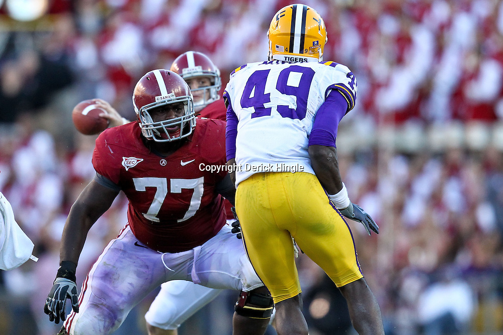 November 6, 2010; Baton Rouge, LA, USA; Alabama Crimson Tide offensive linesman James Carpenter (77) blocks against LSU Tigers defensive end Barkevious Mingo (49) during the second half at Tiger Stadium. LSU defeated Alabama 24-21.  Mandatory Credit: Derick E. Hingle