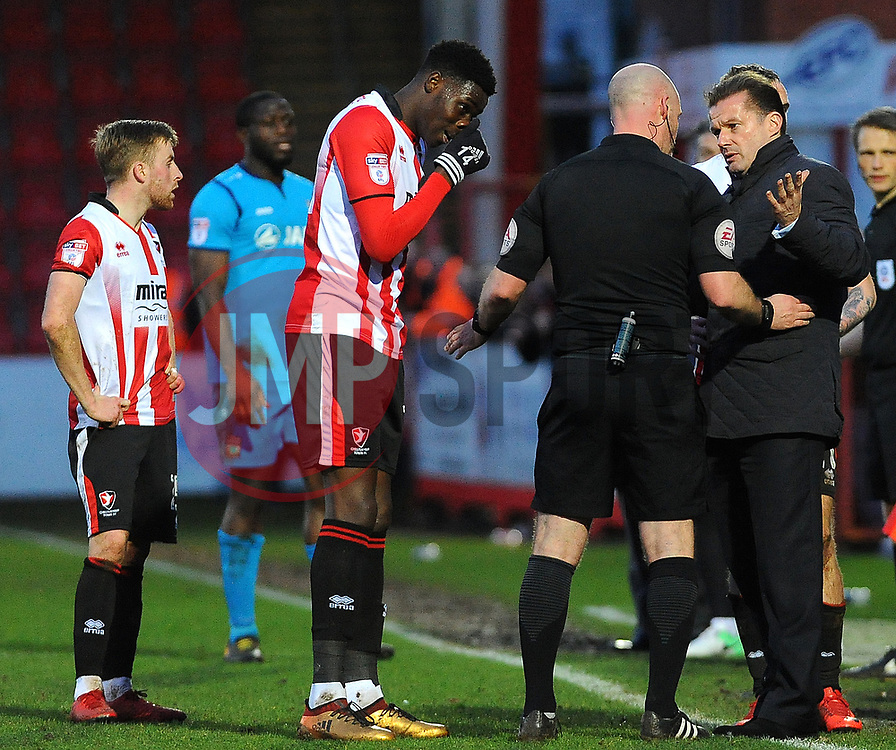 Referee Kevin Johnson has words with Elijah Adebayo of Cheltenham Town and Barnet manager Graham Westley- Mandatory by-line: Nizaam Jones/JMP- 27/01/2018 - FOOTBALL - LCI Rail Stadium- Cheltenham,England - Cheltenham Town v Barnet -Sky Bet League Two