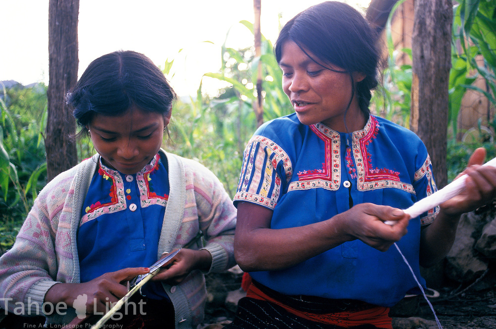 An indigenous Tzotzil woman and her daughter, who were expelled from her community of San Juan Chamula for being evangelical, as opposed to Catholic, weaves on a backstrap loom in her neighborhood of La Hormiga, above San Cristobal de las Casas, Chiapas,Mexico.