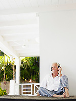 Man wearing headphones sitting on verandah