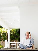 Man wearing headphones sitting on verandah