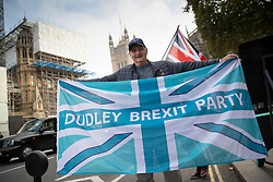© Licensed to London News Pictures. 31/10/2019. London, UK. A man carries a Union flag with the words 'Dudley Brexit Party' as protestors gather near Parliament on what would have been the United Kingdom's last day as a member of the European Union. The date of Brexit had been moved to January 31, 2020 after MPs failed to pass Prime Minister Boris Johnson's withdrawal agreement. Photo credit: Peter Macdiarmid/LNP