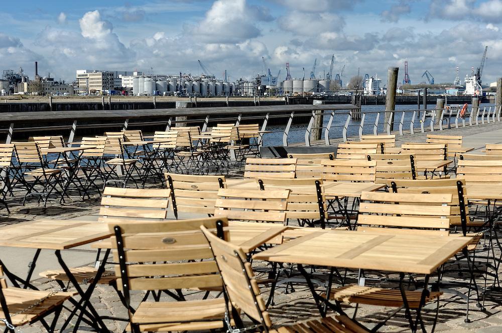 Frühling am Hafen Hamburg in der Hafencity. Tische und Stühle sind im Freien aufgestellt.