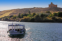 boat cruising on the river nile with Aga Khan tomb on the shore near aswan in egypt
