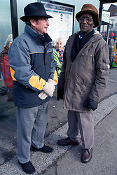 Two men waiting at a bus stop,