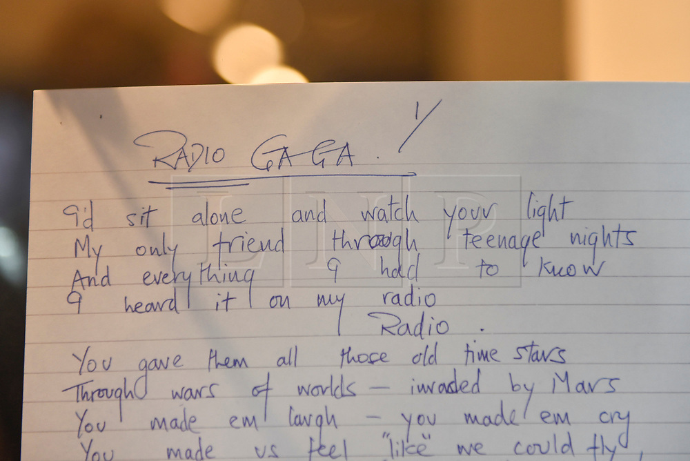 "© Licensed to London News Pictures. 18/10/2018. LONDON, UK. Roger Taylor's original handwritten song lyrics to ""Radio Ga Ga"" on display. A Queen pop-up shop has opened in Carnaby Street.  Coinciding with the release next week of the movie ""Bohemian Rhapsody"", the shop offers Queen music fans memorabilia, a display of stage costumes as well as archived Queen performance footage.  Photo credit: Stephen Chung/LNP"