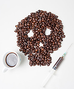 caffein addiction concept. Coffee beans in the shape of a skull and a syringe of caffeine