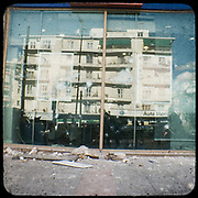 The reflection of a typical 1960&rsquo;s Athenian building on a bank&rsquo;s broken front glass in Alexandras avenue, Athens. <br /> <br /> Following the murder of a 15 year old boy, Alexandros Grigoropoulos, by a policeman on 6 December 2008 widespread riots, protests and unrest followed lasting for several weeks and spreading beyond the capital and even overseas<br /> <br /> When I walked in the streets of my town the day after the riots I instantly forgot the image I had about Athens, that of a bustling, peaceful, energetic metropolis and in my mind came the old photographs from WWII, the civil war and the students uprising against the dictatorship. <br /> <br /> Thus I decided not to turn my digital camera straight to the destroyed buildings but to photograph through an old camera that worked as a filter, a barrier between me and the city.
