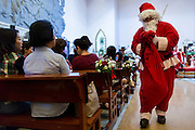 Santa Claud delivers candy to parishioners during Christmas services at Holy Redeemer Church in Bangkok. Thailand is predominantly Buddhist but Christmas is widely celebrated throughout the country. Buddhists mark the day with secular gift giving but there are about 300,000 Catholics in Thailand who celebrate religious Christmas. Catholics first came to Thailand (then Siam) in 1567 as chaplain for Portuguese mercenaries in the employ of the Siamese monarchy. There has been a continuous Catholic presence in Thailand since then.