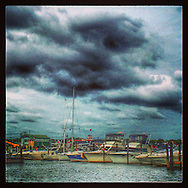 West Sayville, NY: September 9, 2014--- Storm clouds hover over pastel colored boats in the Sayville marina.  © Audrey C. Tiernan