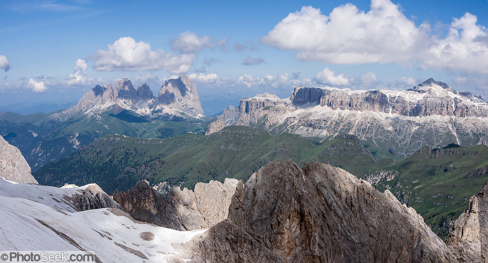 See Langkofel/Sassolungo and Sella Groups from the Marmolada lift, in the Dolomites, Italy. From Malga Ciapela village, take a spectacular lift on Marmolada (Queen of the Dolomites) above the biggest (and only skiable) glacier in the Dolomiti: Ghiacciaio della Marmolada. Known as Marmoleda in Ladin, the highest peak in the Dolomites rises to 3343 meters (10,968 feet) elevation. Top station Punta Rocca gives a very exciting view of the surrounding mountains. The World War I museum at Serauta lift station describes the amazing City of Ice (Die Eisstadt, 1917), where Austrian soldiers inside the Marmolada Glacier built quarters in tunnels extending 12 kilometers with a vertical drop of over 1000 meters! Nine thousand Austrian and Italian soldiers died on the front line in a stalemate at Marmolada over 2 years. After Austria lost World War I, its South Tirol became Italy's Trentino-Alto Adige/Südtirol region (bordering the Veneto). Find lift info at Funiviemarmolada.com. The Dolomites are part of the Southern Limestone Alps, Europe. UNESCO honored the Dolomites as a natural World Heritage Site in 2009. This panorama was stitched from 2 overlapping photos.