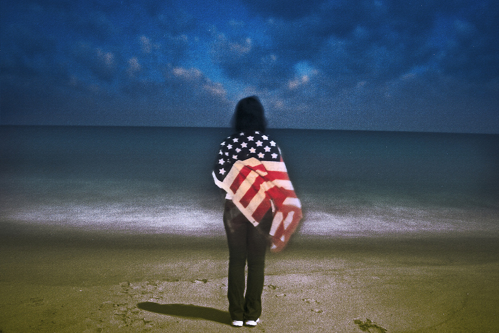 A figure looking out to sea holding a US flag standing on a beach under stormy sky