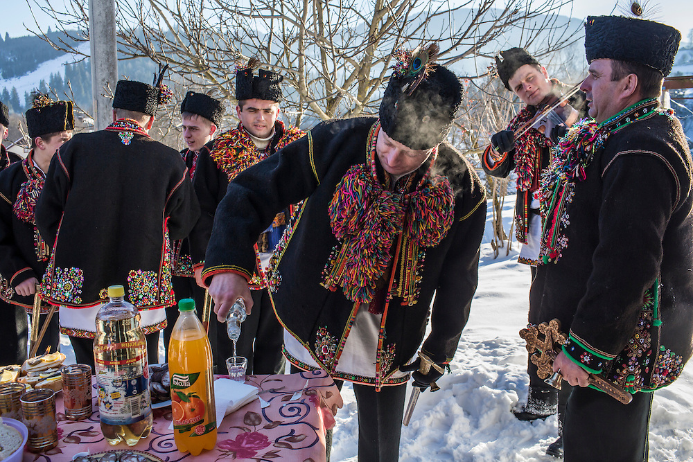ILTSI, UKRAINE - JANUARY 7: Men wearing traditional Hutsul clothing eat and drink snacks and vodka offered by a local resident after singing for him in celebration of Orthodox Christmas on January 7, 2015 in Iltsi, Ukraine. The men gather in groups and travel house to house for twelve days singing songs until they've visited every home in the village. (Photo by Brendan Hoffman/Getty Images) *** Local Caption ***
