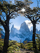 "Mount Fitz Roy (3405 meters or 11,170 feet) rises abruptly above a forest of Southern Beech (Lenga or Nothofagus) in the southern Andes mountains, near El Chaltén village, in Los Glaciares National Park, Argentina, South America. In 1877, explorer Perito Moreno named ""Cerro Fitz Roy"" for Robert FitzRoy (no space before the capital R) who, as captain of the HMS Beagle, had travelled up the Santa Cruz River in 1834 and charted much of the Patagonian coast. First climbed in 1952 by French alpinists Lionel Terray and Guido Magnone, Mount Fitz Roy has very fickle weather and is one of the world's most challenging technical ascents. It is also called Cerro Chaltén, Cerro Fitz Roy, and Monte Fitz Roy (with a space before the R). Chaltén comes from a Tehuelche (Aonikenk) word meaning ""smoking mountain"" (explained by frequent orographic clouds). Cerro is a Spanish word meaning hill. El Chaltén village was built in 1985 by Argentina to help secure the disputed border with Chile, and now tourism supports it, 220 km north of the larger town of El Calafate. The foot of South America is known as Patagonia, a name derived from coastal giants, Patagão or Patagoni, who were reported by Magellan's 1520s voyage circumnavigating the world and were actually Tehuelche native people who averaged 25 cm (or 10 inches) taller than the Spaniards. Mount Fitz Roy is the basis for the Patagonia company's clothing logo, after Yvon Chouinard's ascent and subsequent film in 1968."