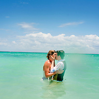Dan and Casi share a kiss at their trash the dress session in Xpuha, Mexico.