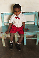 Sri Lanka - Shy Kandy School boy in red boytie and shorts sitting on blue chairs