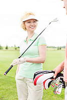Happy woman looking at male friend at golf course