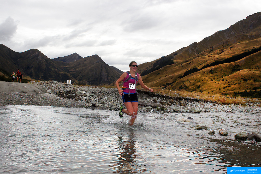 Runner Sue Charlesworth crosses Moke Creek on the Ben Lomond High Country Station during the Pure South Shotover Moonlight Mountain Marathon and trail runs. Moke Lake, Queenstown, New Zealand. 4th February 2012. Photo Tim Clayton