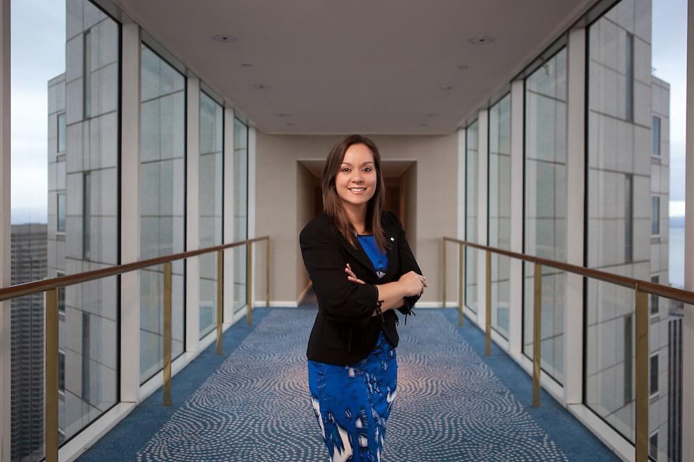 Picture of Business Female and Environmental Portrait in San Francisco high rise, interior Hallway. Blue sky, carpeting and dress in white building.
