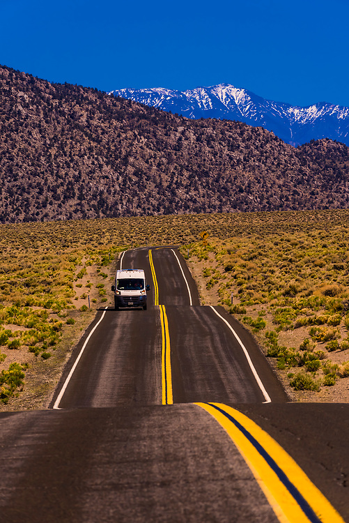 A camper van passing over Highway 120 in California after coming from Nevada with the Sierra Nevada Mountains behind, USA.