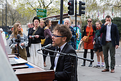 London, UK. 16th April 2019. A climate change activist from Extinction Rebellion plays the piano at Marble Arch on the second day of International Rebellion activities to call on the British government to take urgent action to combat climate change.