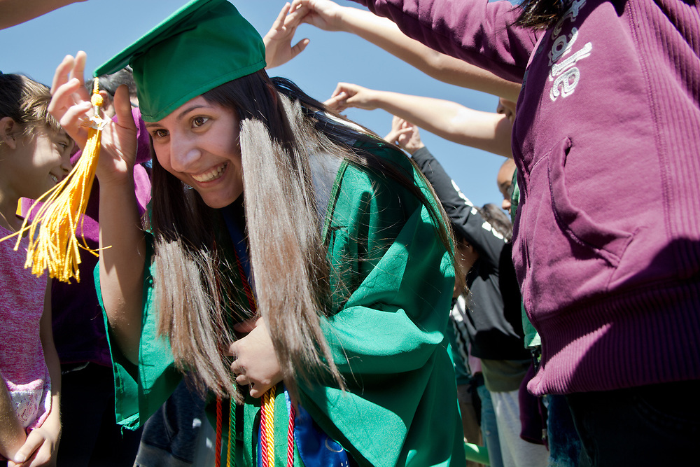 mkb051217a/metro/Marla Brose -- Albuquerque High graduating senior Odalys Marquez smiles as she crouches down to go through a gauntlet of students from East San Jose Elementary, Friday, May 12, 2017, in Albuquerque, N.M. The school's students cheered on a group of graduates as they walked around the school which was decorated with congratulations. The graduates are visiting other schools in their cluster to visit with young students and offer them a view of graduation. Albuquerque High School graduation ceremony will be Monday, May 15. (Marla Brose/Albuquerque Journal)