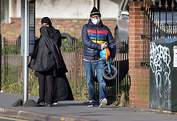 © Licensed to London News Pictures. 09/03/2020. London, UK . A man wears a face mask as he carries a child's helmet and bicycle at Selhurst Park in south London. New cases of the COVID-19 strain of Coronavirus are being reported daily in the UK. Photo credit: Peter Macdiarmid/LNP