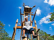 22 JULY 2016 - TENGANAN DUAH TUKAD, BALI, INDONESIA: Men play on human powered ferris wheel and swing before the Pandanus fights in the Tenganan Duah Tukad village on Bali. The ritual Pandanus fights are dedicated to Hindu Lord Indra. Men engage in ritual combat with spiky pandamus leaves and rattan shields. They usually end up leaving bloody scratches on the combatants' backs. The young girls from the community wear their best outfits to watch the fights. The fights have been traced to traditional Balinese beliefs from the 14th century CE. The fights are annual events in the Balinese year, which is 210 days long, or about every seven months in the Gregorian calendar.    PHOTO BY JACK KURTZ