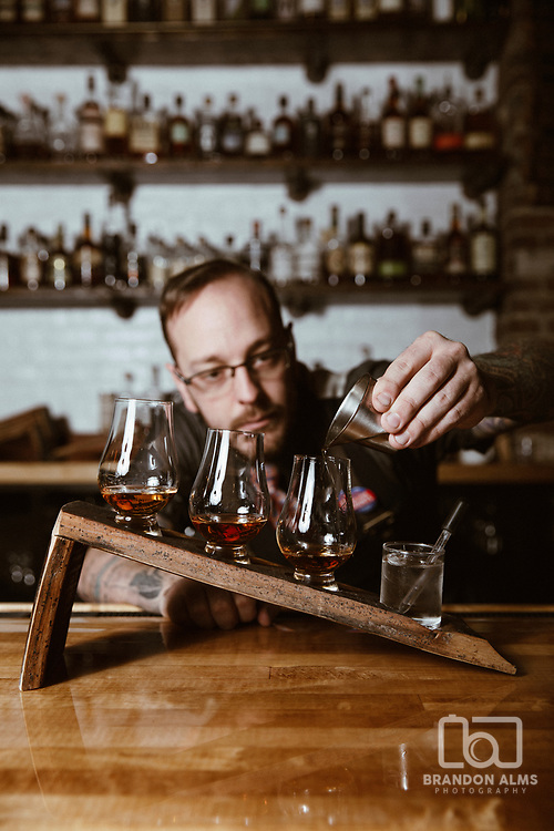 Bartender pouring a whiskey flight at CB Social House located in Springfield, MO