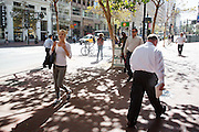 Een meisje loopt al bellend over Market Street in San Francisco. De Amerikaanse stad San Francisco aan de westkust is een van de grootste steden in Amerika en kenmerkt zich door de steile heuvels in de stad.<br /> <br /> A girl is walking while on the phone at Market Street in San Francisco. The US city of San Francisco on the west coast is one of the largest cities in America and is characterized by the steep hills in the city.