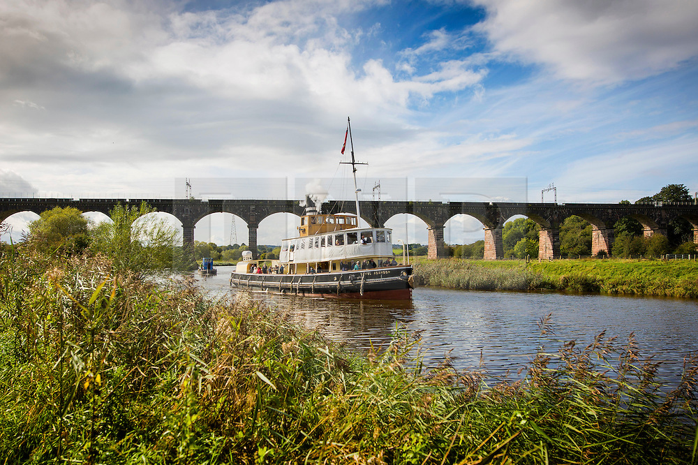 "© Licensed to London News Pictures. 30/09/2016. Bartington UK. Picture shows the Daniel Adamson making it's way under the Dutton rail viaduct on the River Weaver on it's maiden voyage after a £5M renovation. The Daniel Adamson steam boat has been bought back to operational service after a £5M restoration. The coal fired steam tug is the last surviving steam powered tug built on the Mersey and is believed to be the oldest operational Mersey built ship in the world. The ""Danny"" (originally named the Ralph Brocklebank) was built at Camel Laird ship yard in Birkenhead & launched in 1903. She worked the canal's & carried passengers across the Mersey & during WW1 had a stint working for the Royal Navy in Liverpool. The ""Danny"" was refitted in the 30's in an art deco style. Withdrawn from service in 1984 by 2014 she was due for scrapping until Mersey tug skipper Dan Cross bought her for £1 and the campaign to save her was underway. Photo credit: Andrew McCaren/LNP"
