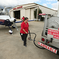 Tiffany Heavner puts up the fuel hose after refueling a plane at the Tupelo airport Monday afternoon.