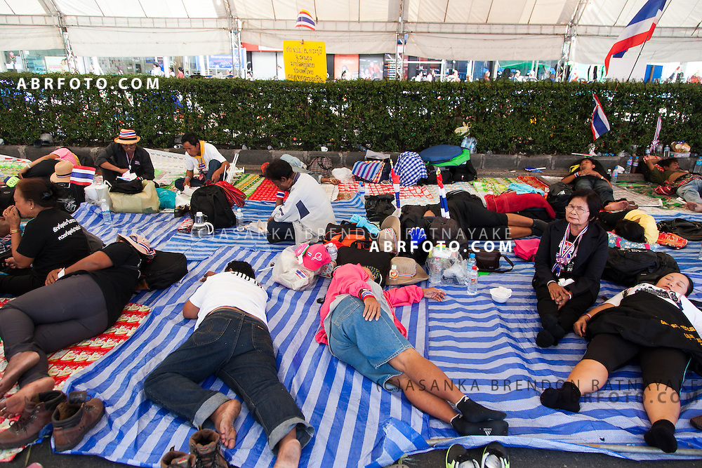 Anti-Thai government protestors (PDRC) sleep on makeshift matts while camped at a protest site.